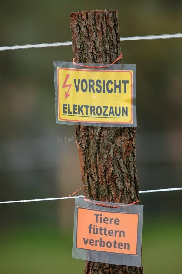 在电篱芭的警告标记 免版税库存图片