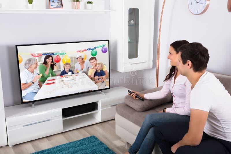 在电视上的夫妇观看的生日庆祝 库存照片