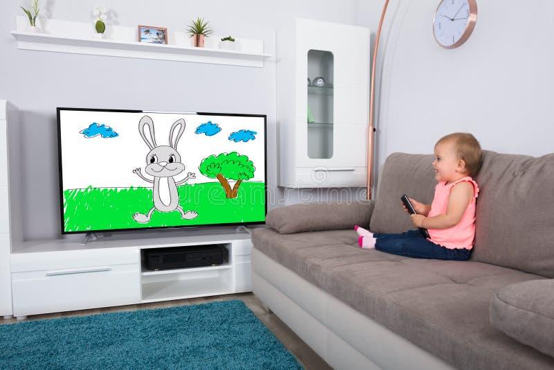 在电视上的女婴观看的动画片 图库摄影