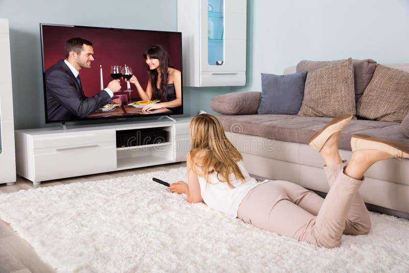 在电视上的妇女观看的电影 免版税库存图片