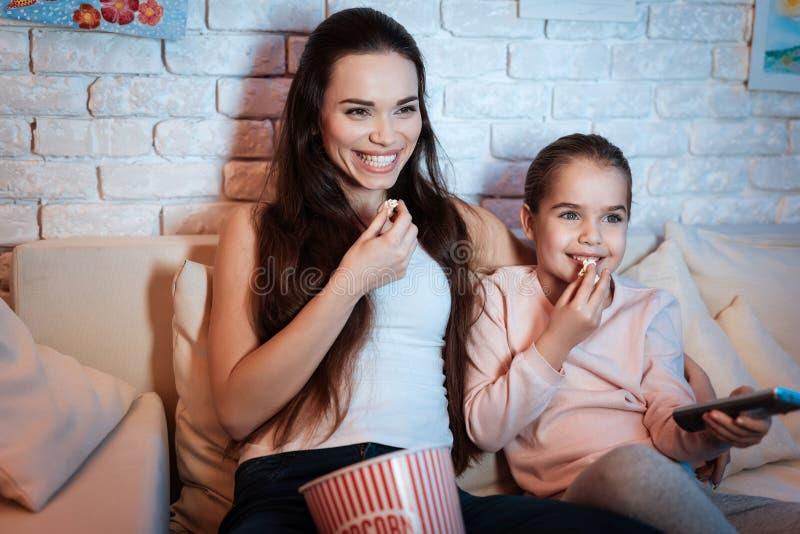 在电视上的母亲和女儿观看的电影在晚上在家 库存照片
