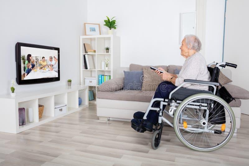 在电视上的祖母观看的电影 免版税库存图片