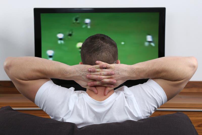 年轻在电视的人观看的橄榄球 库存图片