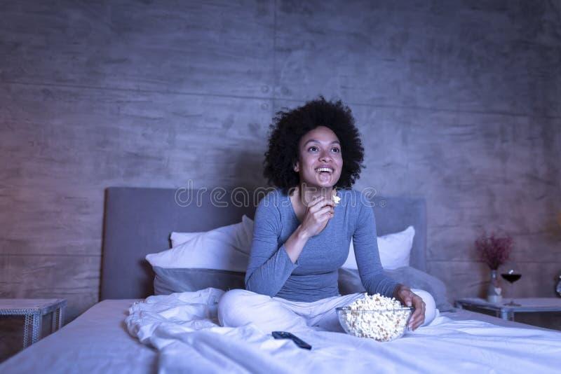 在电视的妇女观看的喜剧 库存照片