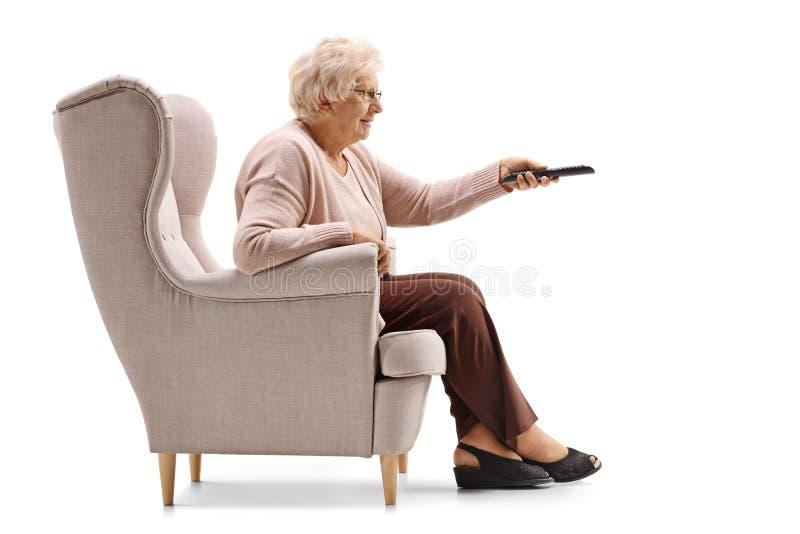 在电视的扶手椅子改变的渠道安装的年长妇女 库存照片