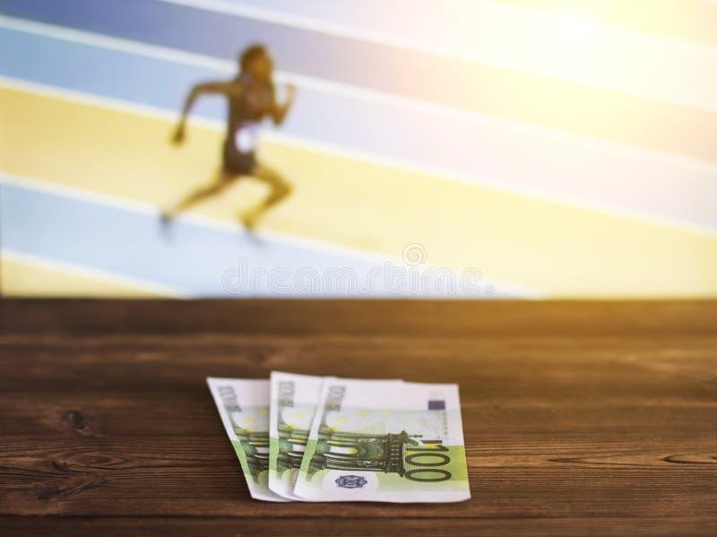 在电视的背景的欧元金钱在哪展示田径运动竞技的,跑步,打赌的体育,欧元 免版税库存照片
