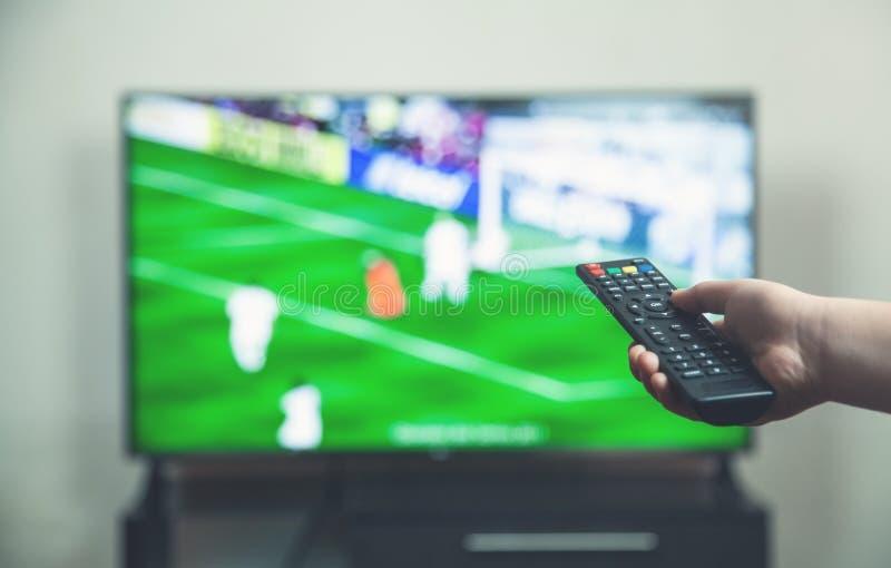 在电视的观看的足球比赛与遥远的控制器 免版税库存照片