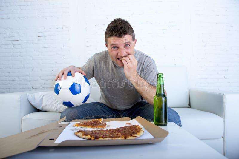 年轻在电视紧张和激动的痛苦重音尖酸的指甲盖的人观看的橄榄球赛在沙发 免版税库存图片