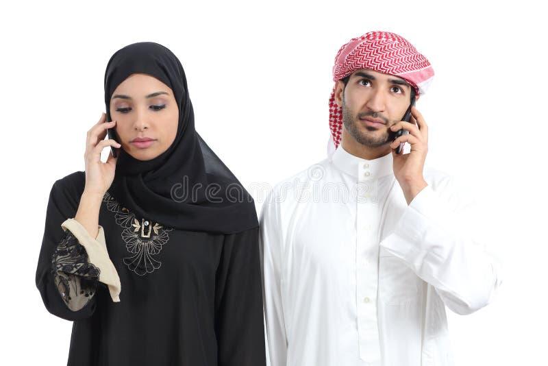 在电话憎恶的阿拉伯夫妇 图库摄影