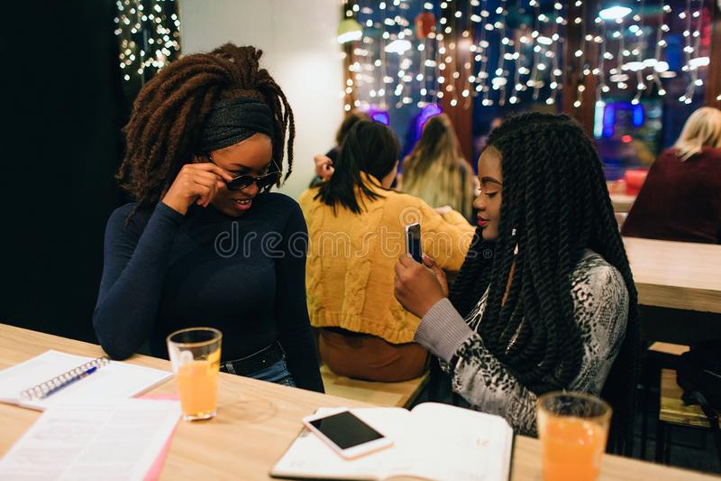 在电话照相机的一个非洲式样姿势 她握在sungalsses的手 第二个式样举行电话和拍照片 他们坐 免版税库存图片