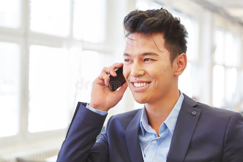 在电话的亚洲商人 免版税库存图片