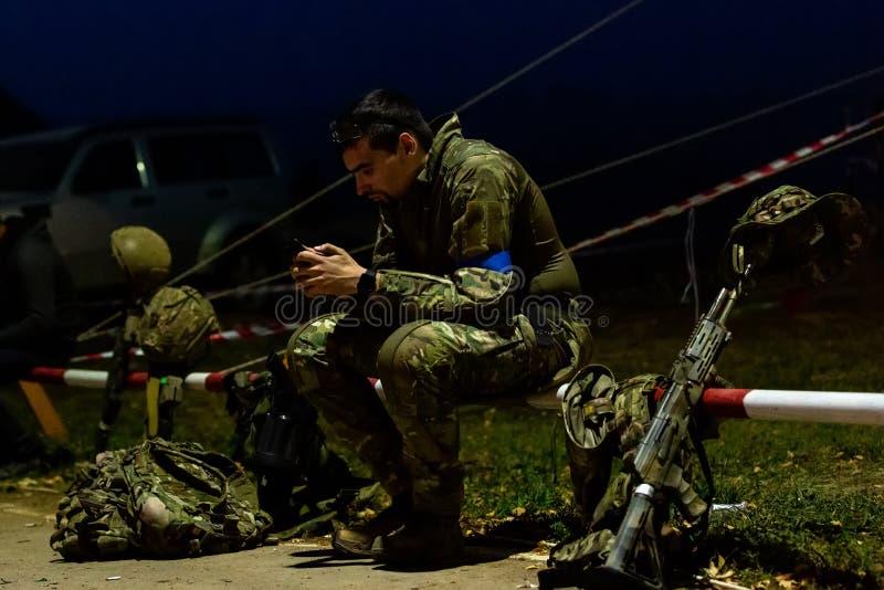 在电话的侧视图严肃的战士文字消息,当佩带在制服和围拢由武器时 技术和 免版税库存图片