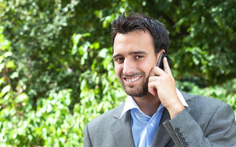 在电话的可爱的拉丁商人在公园 免版税库存图片