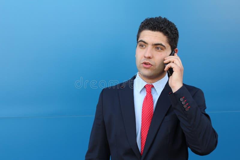 在电话的吃惊的年轻商人 免版税库存照片