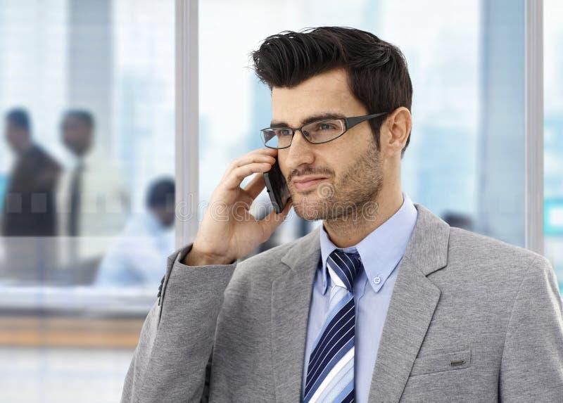 在电话的商人在办公室 免版税图库摄影