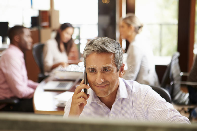 在电话的商人在有会议的书桌在背景中 免版税图库摄影