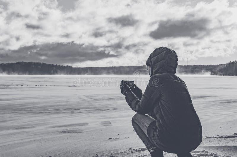 在电话的女孩照片一个冻湖 库存照片