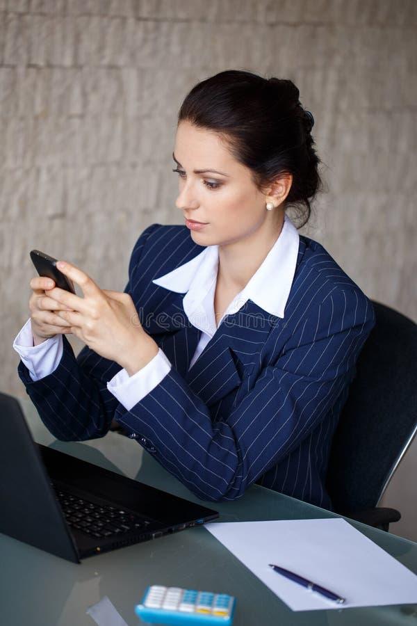 在电话的女实业家键入的消息在办公室 免版税库存图片