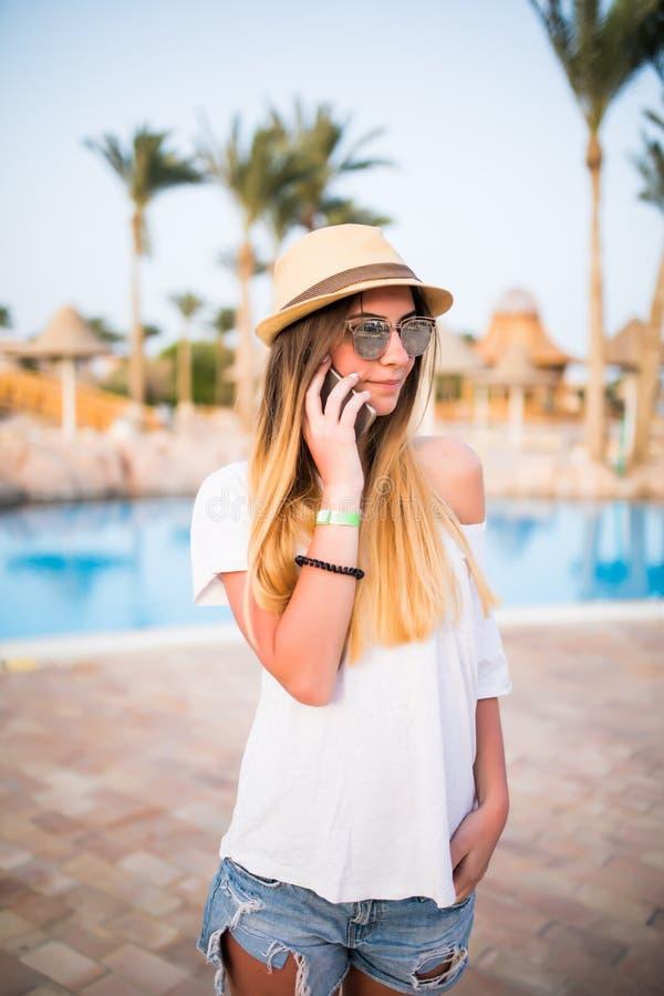 在电话的妇女答复在夏天职业的游泳池附近 库存图片