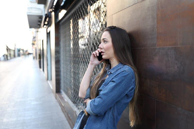 在电话的妇女谈话在街道 免版税图库摄影