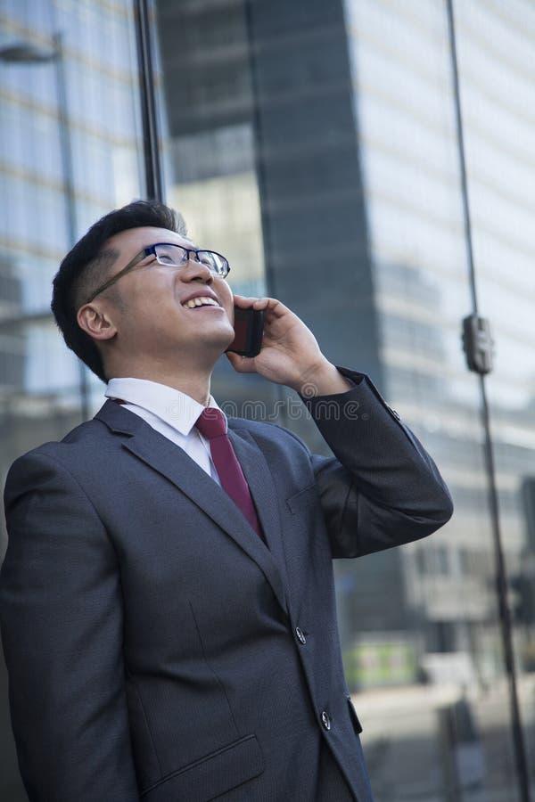 在电话的微笑的商人外面在查寻的北京 库存照片