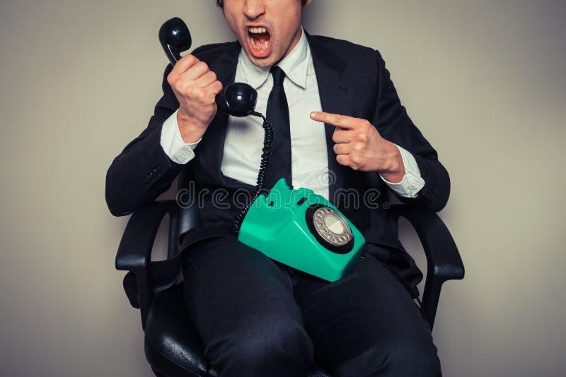 在电话的恼怒的商人 免版税库存照片