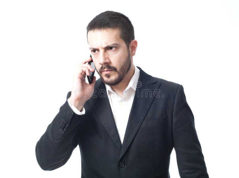 在电话的恼怒的年轻商人 库存图片