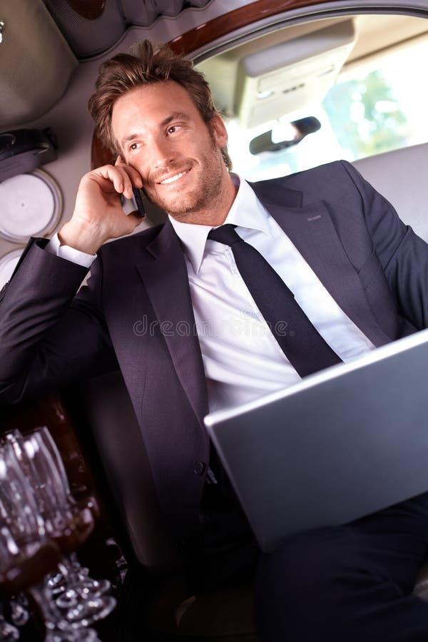 在电话的愉快的生意人在大型高级轿车 免版税库存照片