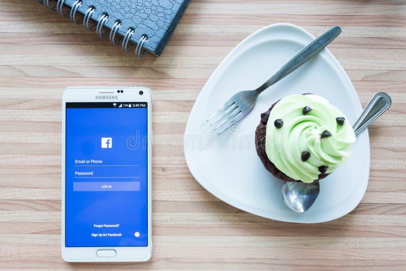 在电话的戏剧facebook在咖啡店 免版税库存照片