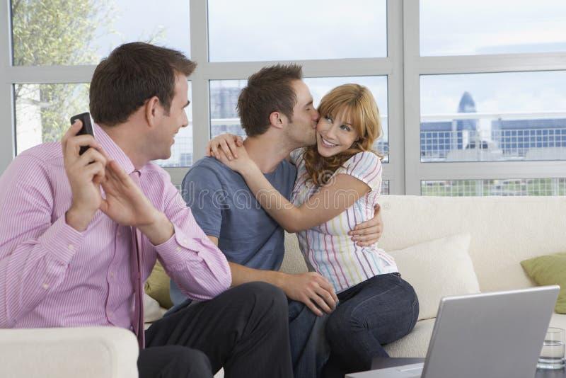 在电话的房地产开发商由亲吻的夫妇在新的家 免版税库存图片