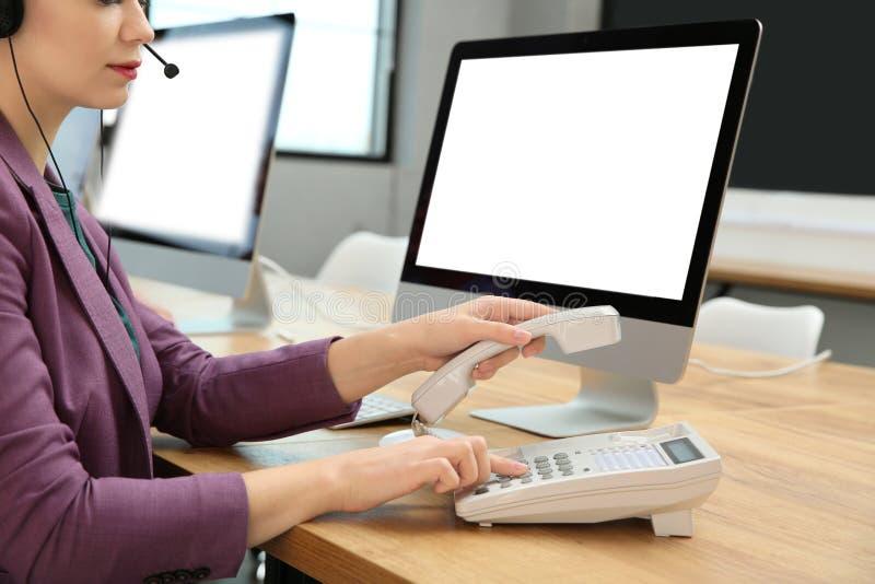 在电话的技术支持操作员拨的数字在桌上, 免版税库存图片