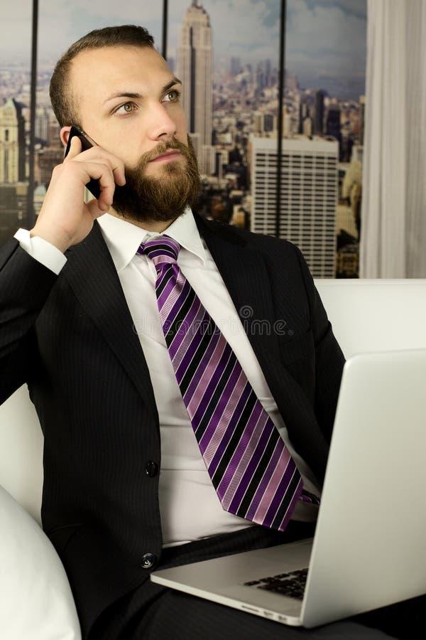 在电话的担心的商人在办公室 库存照片