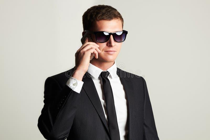 在电话的生意人 衣服和太阳镜的英俊的人 免版税库存照片