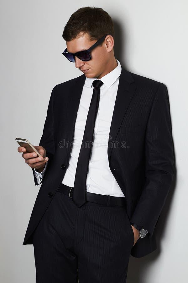 在电话的生意人 衣服和太阳镜的英俊的人 免版税图库摄影