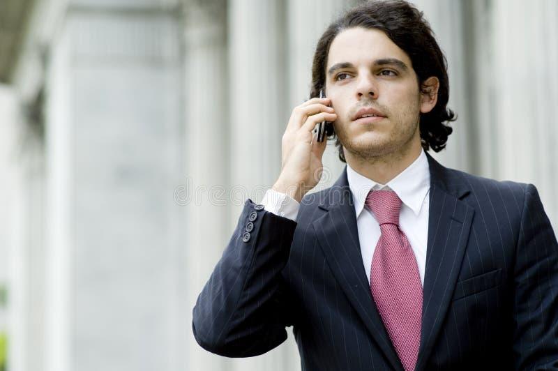 在电话的生意人 免版税库存照片