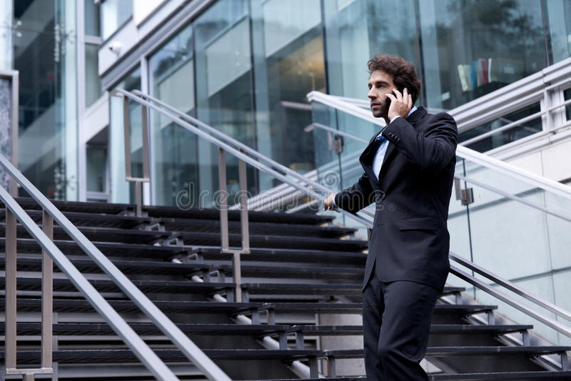 在电话的骄傲的商人在他的办公室前面 库存图片