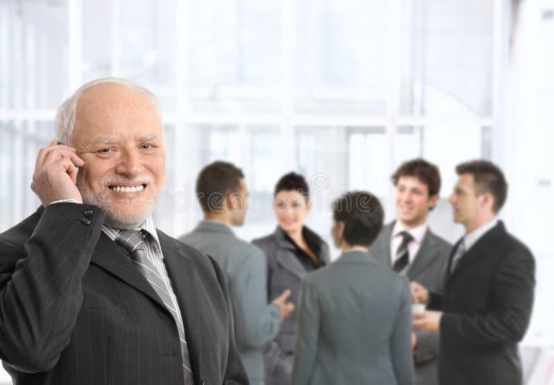 在电话的高级生意人在办公室大厅 免版税库存照片
