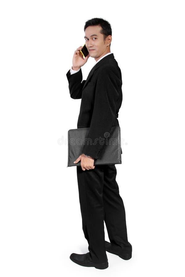 在电话,转动的面孔的商人  免版税图库摄影