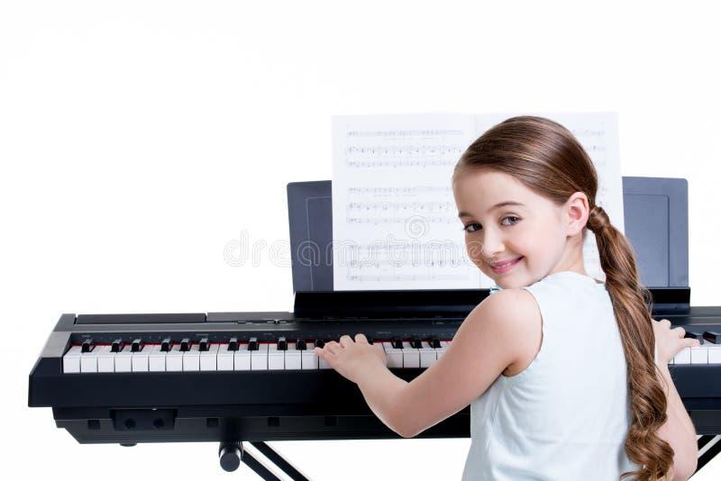 在电钢琴的微笑的女孩戏剧。 免版税库存照片