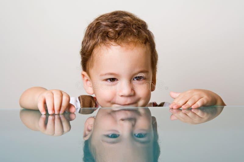 在男孩玻璃小的表之后 免版税库存照片