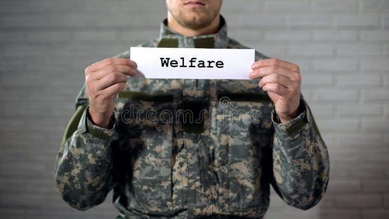 在男性战士,经济援助,支持的标志手写的福利救济词 免版税图库摄影