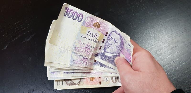 在男性捷克金钱钞票移交黑背景 免版税库存图片