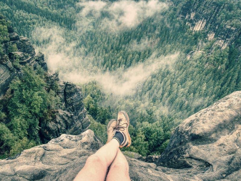 在男性赤裸腿的看法到有薄雾的谷里 在足迹的休息 免版税库存图片