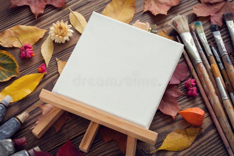 在画架、油漆管、刷子绘的和秋叶的帆布在书桌上 免版税图库摄影