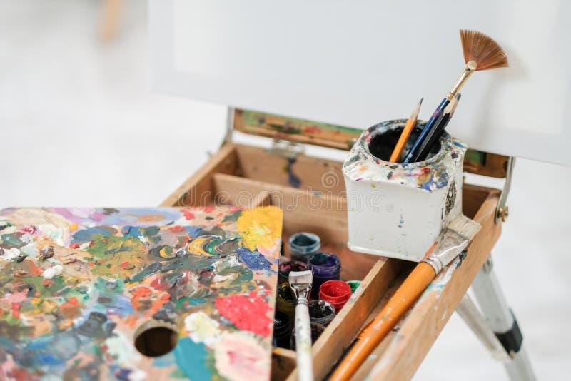 在画架的艺术家的工具 刷子、油漆和帆布 库存图片