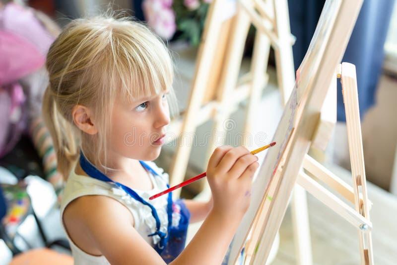 在画架的逗人喜爱的白肤金发的微笑的女孩绘画在艺术演播室的车间教训 孩子藏品刷子在手中和有乐趣图画与 免版税库存图片