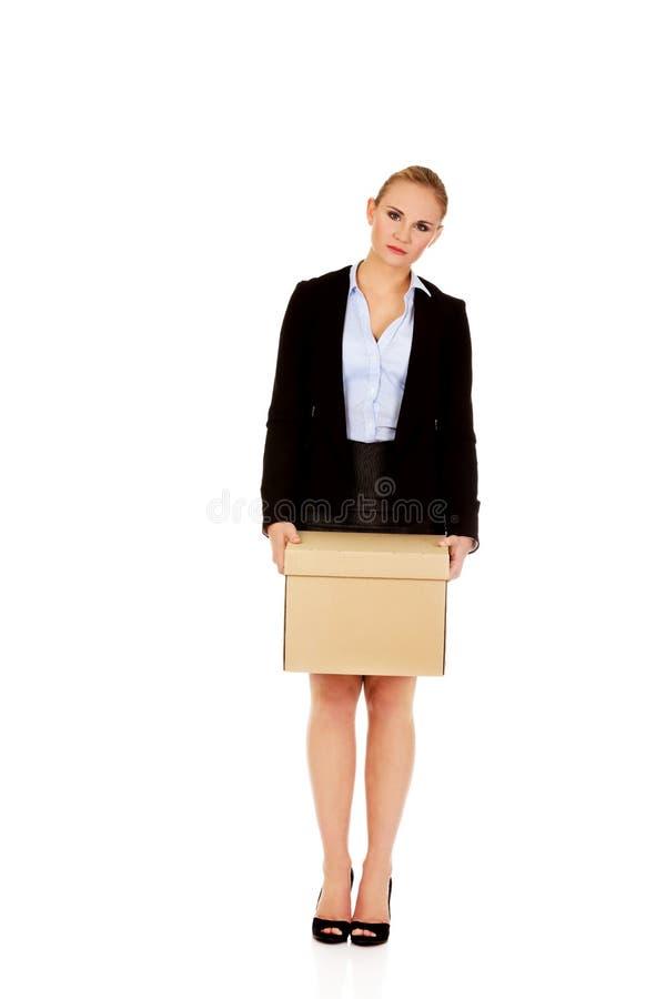在疏松工作以后的哀伤的女商人运载的箱子 免版税库存照片