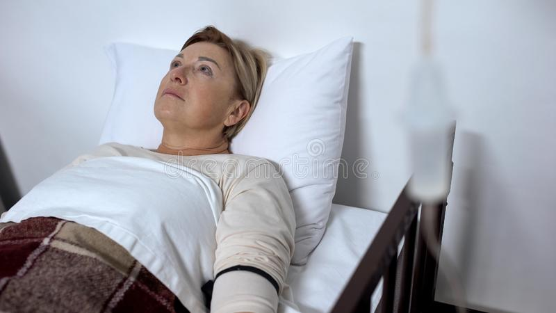 在病床的哀伤的年迈的患者在吸管,患者控制痛觉缺失下 免版税图库摄影