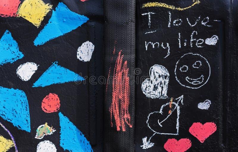 """在白垩的题字-""""我爱我的在黑背景的生活""""和图画 库存照片"""