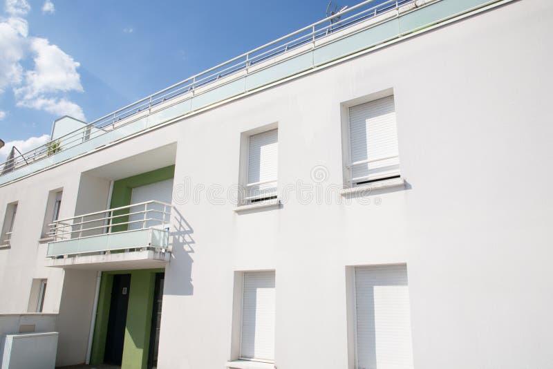 在白天公寓公寓房期间的外部典型的建立的大厦白色门面 免版税库存图片